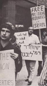 فوزي الأسمر في مظاهرة امام القنصلية الاسرائيلية في نيو يورك ٬ 1975 ٬ وهو يحمل اللافتة باللغة العبرية تطلب باطلاق سراح المعتقل السياسي رامي لفنه